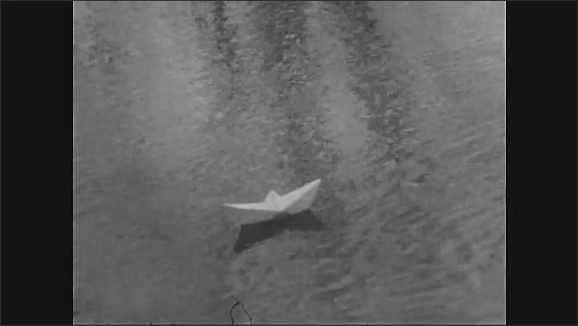 1970s: UNITED STATES: paper boat floats along water. Ripples in water. Reflection of paper boat on water
