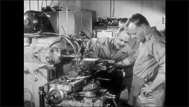 1950s: Men working in factory turn, look back. Man walks to man in front of machine, talks to man, gestures, scolds man. Man adjusts machine. Man sits at desk, flips through papers on clipboard.