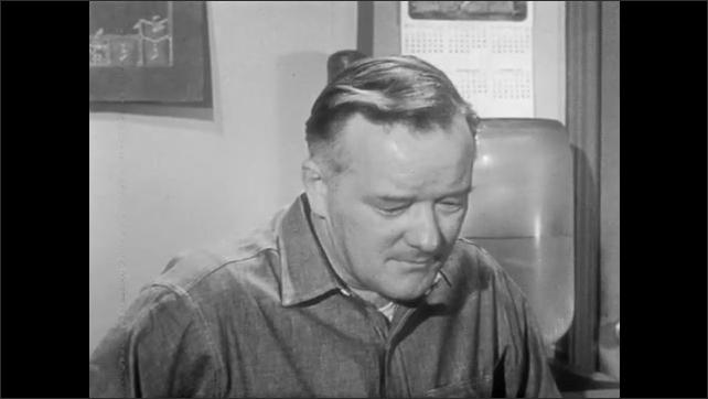 1950s: Two men sit in office, talk. Man lights cigarette.