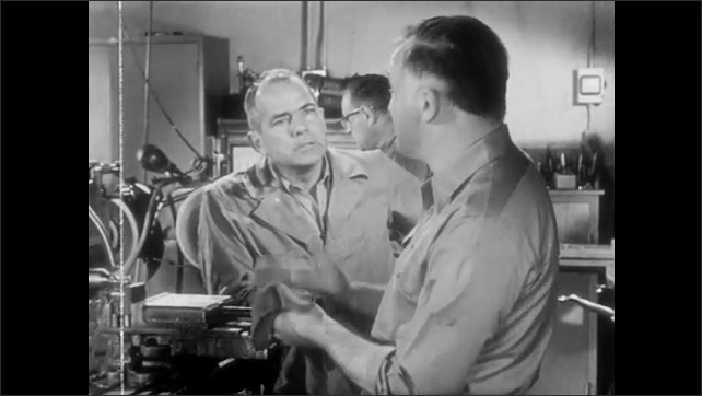 1950s: Man looks down at crate on floor marked rush. Man angrily talks to man at machine.