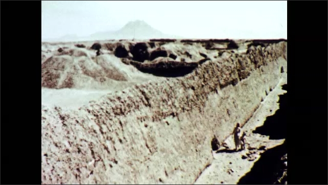 1960s: A woman and a child walk in the middle of ancient Inca adobe walls.