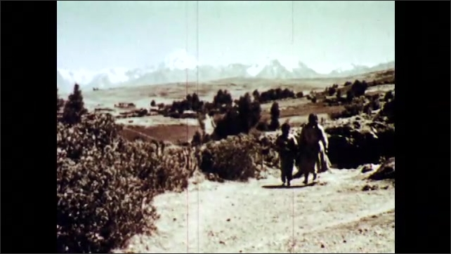 1960s: A girl and boy walk next to fields with mountains in background. Boy and girl hold notebooks and walk through a gate made of stone. A girl and boy walk next to an ancient stone wall.
