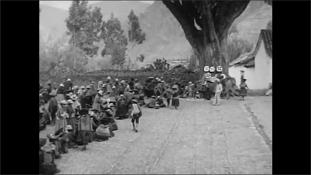 1940s: woman picks potatoes off blanket. men look at hats on tree trunk. men and women walk around marketplace in village. woman herds llamas off field near Andes Mountains and down dirt road.