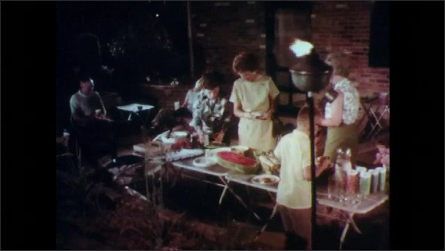 1960s: UNITED STATES: salad in bowl. Hand picks up hot corn on cob. Family eat in back yard.