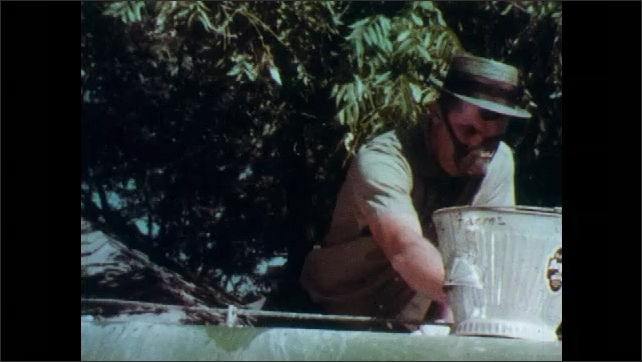 1960s: UNITED STATES: man fills tractor tank with insecticide from bottle. Tractor sprays pesticides on crops in field