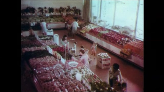 1960s: UNITED STATES: ladies buy fruit and vegetables in grocery store. Lady pulls child in cart. Family eat outdoors at night