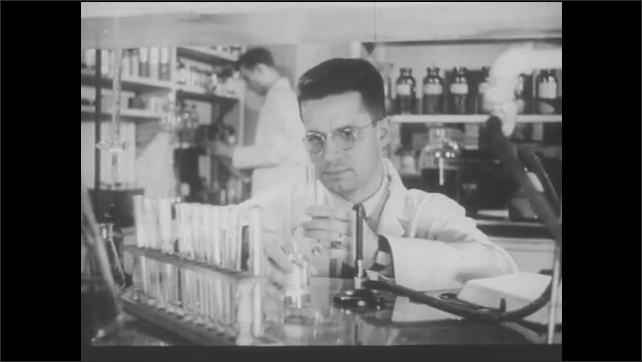 1940s: Pharmacist in chemistry lab pours liquid into vial and shakes it.