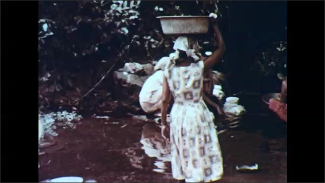 1960s: PHILIPPINES: man and boy plough field with cattle. Ladies wash clothes in river. Girl sits with washer women in river