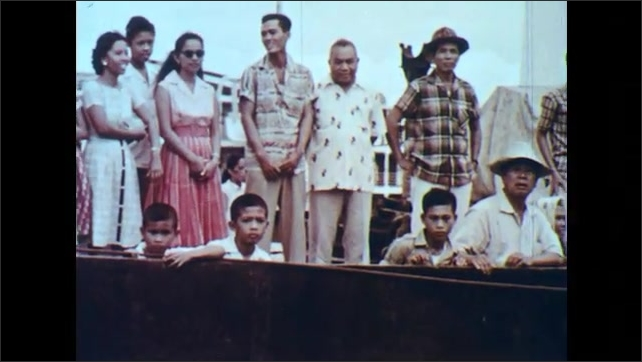 1960s: PHILIPPINES: ship in harbour. Passengers stand on ship deck. Boats on water.