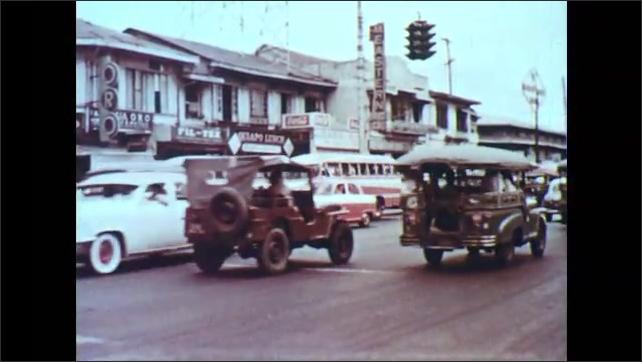 1960s: PHILIPPINES: industrial buildings in Manila. City street in Manila. People cross road. Traffic on road