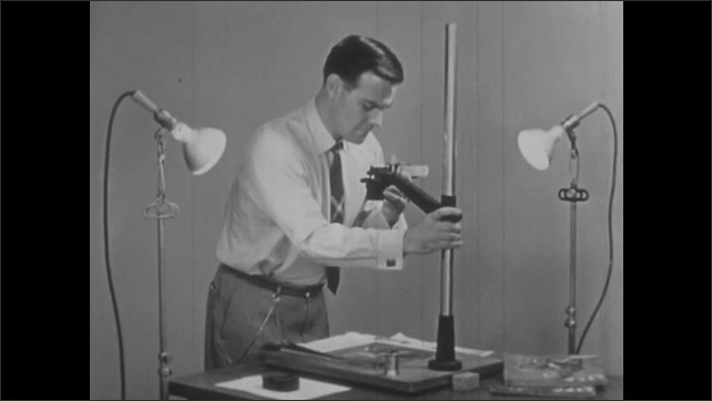 1950s: Teacher sets up copy stand with two reflective lamps for light.