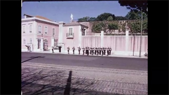 1960s: PORTUGAL: EUROPE: band march along street. Men in uniform stand to attention. Men on guard. Men salute