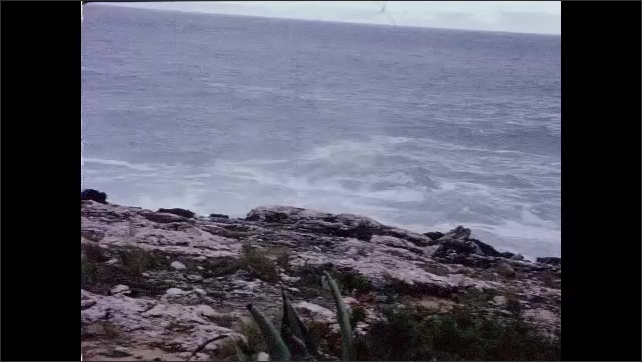 1960s: PORTUGAL: EUROPE: waves crash onto rocks. View along coastline. Lady and man look at view from cliff. Coastal features and waves