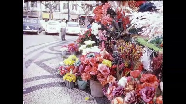 1960s: PORTUGAL: EUROPE: baby in pram by flower stall. Baby chews on dummy. Flowers close up. Decorative floor.