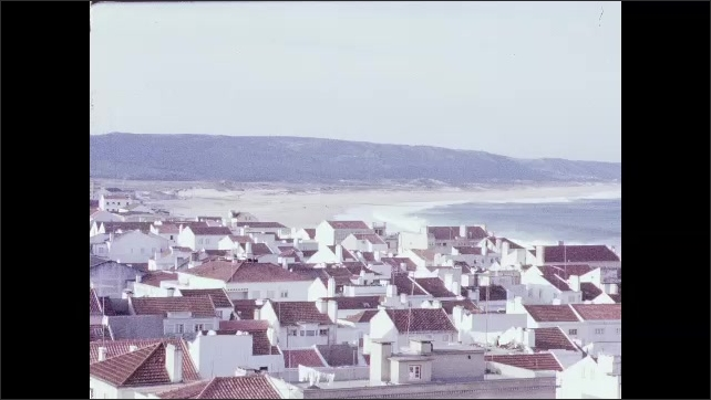 1960s: Mountains.  City by the sea.  Waves crash.