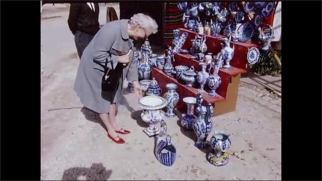 1960s: Church.  Woman admires relief statues on tomb.  Woman looks at plates and talks to shopkeeper.  Mountain.  Women do laundry in river.