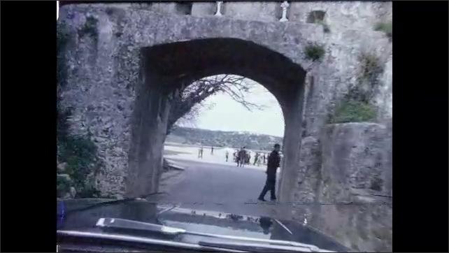 1960s: Church.  Car drives through arch.  City street.  Trees.