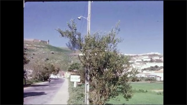 1960s: PORTUGAL: EUROPE: people ride donkeys by side of road. View across landscape from road. Trees by road.