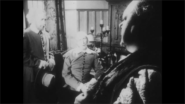 1950s: UNITED STATES: merchants speak in room. Man talks to men in room. Man rubs chin