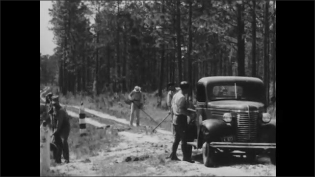 1940s: Man sits at radio communication desk, talking into microphone. Men digging dirt in field run to truck and toss shovels in the back as they climb aboard.