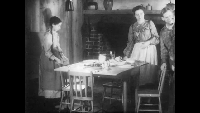 1940s: Mother asks sister to set another place at table. Men take off their deerskin coats. The family and guest sit at dining table and bow their heads.