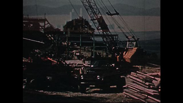 UNITED STATES 1950s: Construction site, crane rotates / Dissolve to view of dam / Dissolve to lake / Dissolve to water exiting dam.
