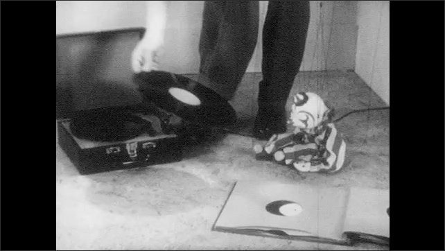 1950s: Marionette sits.  Man turns off phonograph and takes off record.  Man flips through book and puts on record.  Man moves arm onto record.  Puppet stands and walks.