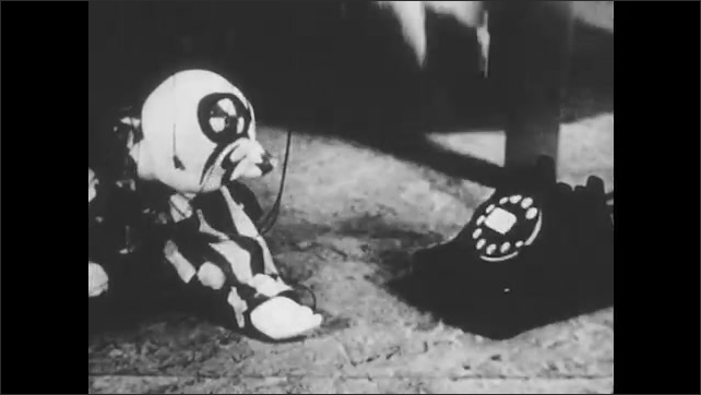 1950s: Marionette clown puppet lays down on floor next to telephone receiver, listens. Man points at phone, dials zero, picks up telephone receiver, puts down receiver. Puppet wiggles around.