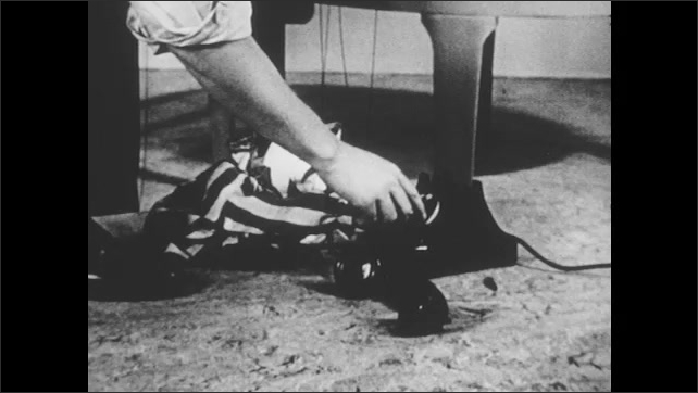 1950s: Marionette clown puppet sits in front of phone. Man bends over, helps puppet dial phone. Puppet stands up, dances, scoots to phone receiver.