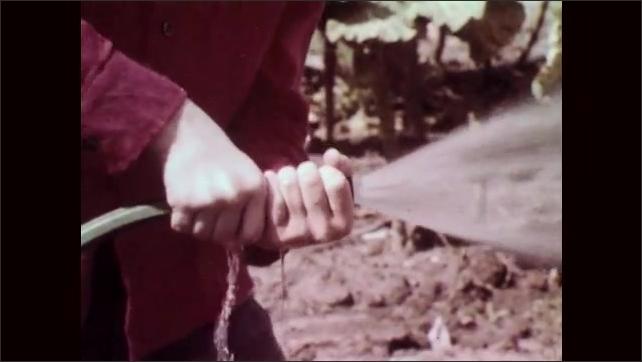 1960s: Boy listens to man talk in crop field. Man talks to boy. Boy sprays ground with water from hose. Man talks to boy. Boy changes spray on hose. Man talks. Girl kneels on ground with basket.