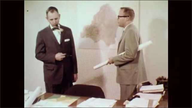 1960s: Black and red dots on map of United States. Red dots increase, black dots decrease. Two men stand in room with map on wall, talking. Man look at map on desk. Illustration of tributaries.