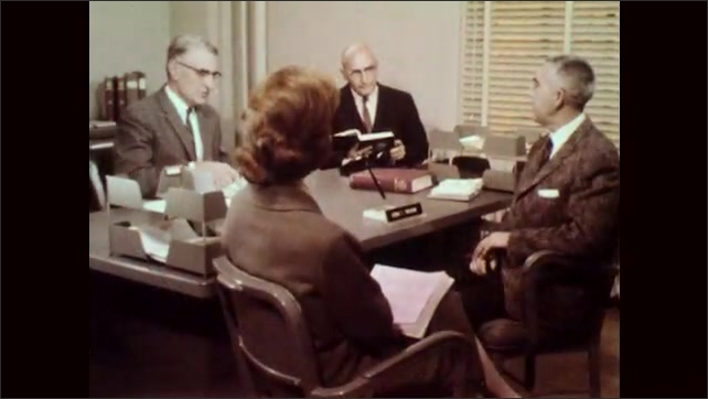 1960s: Man gives presentation in meeting room, pointing to maps on wall. People talk sitting at desk. Two people at desk talking. Woman works at drafting table. People work on drafting tables. Sign.