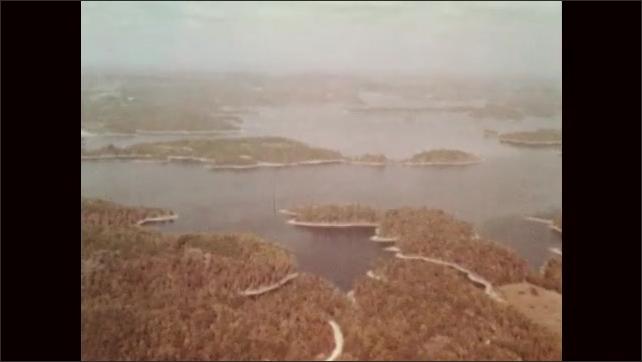 1960s: City lights at night. Waterways in forest area. Man walks along ridge of rocky landscape.