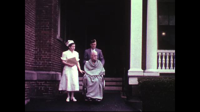 A nurse and transporter take an elderly patient outside on a wheelchair.