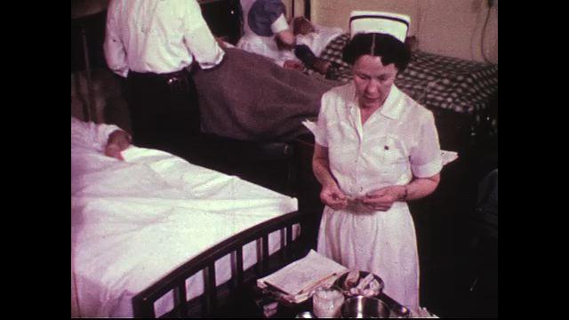 A nurse primes a syringe while an aid takes the temperature of a plane crash victim.