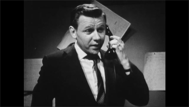 1960s: Man in suit jacket and tie speaks on the telephone.