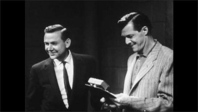1960s: Planner and man talk and man makes note on clipboard. Group of planner walks over to radio device.