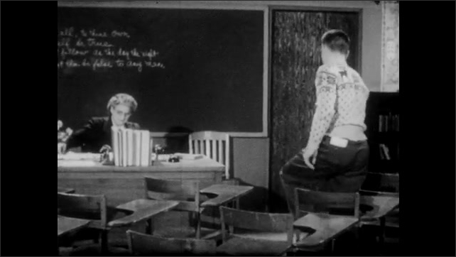 1950s: Young man in reindeer sweater stands up from desk and approaches teacher at front of classroom. Teacher gestures at chair, and student pulls up chair and sits down. Teacher speaks.