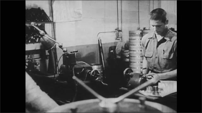 1950s: Machine parts moving, tilt up to man working, pan to men in factory. Men working with surveying equipment.