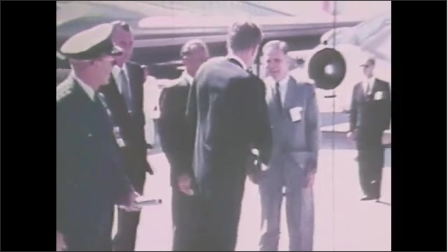 1980s: President John F. Kennedy greets people on tarmac, shakes hands. Convertible car drives on road. Kennedy watches space shuttle on launch pad.