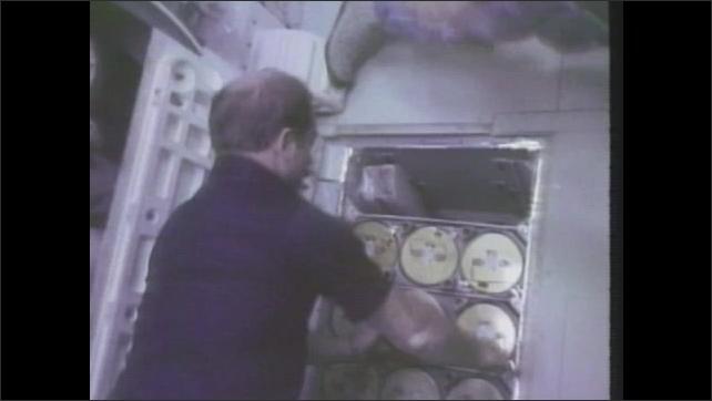 1980s: Astronauts work in zero gravity inside space shuttle. Plant grows inside space shuttle.