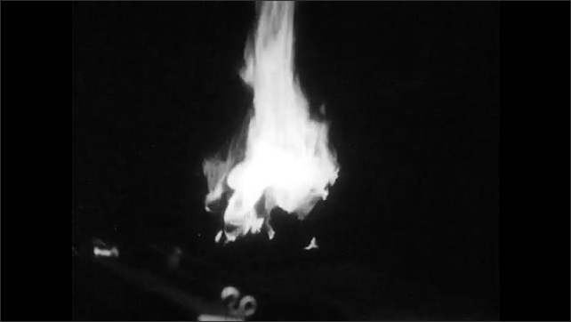 1940s: Man and blacksmith talk. Man holds metal rod in fire, removes rod from fire, hammers metal into curve.