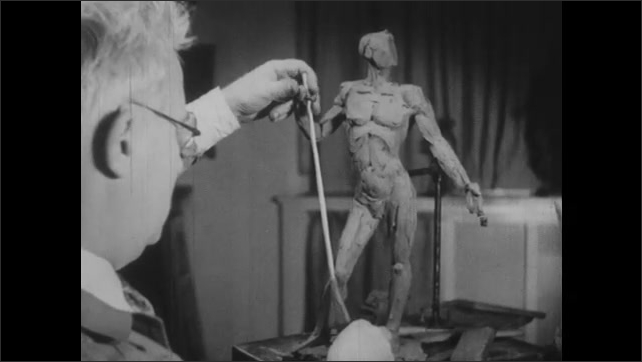 1940s: UNITED STATES: sculptor places stick in hand of clay model