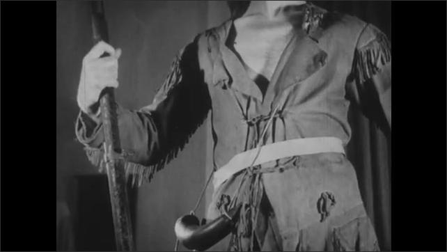 1940s: UNITED STATES: sculptor uses wire tool to carve shoulder fringe on sculpture. Powder horn on model