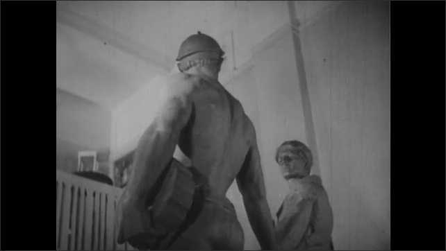 1940s: UNITED STATES: sculptor creates details on clay. Rear view of sculpture