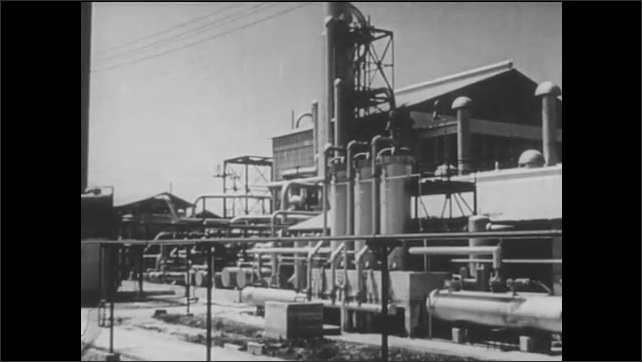 1950s: A man installs a water heater. A refinery.