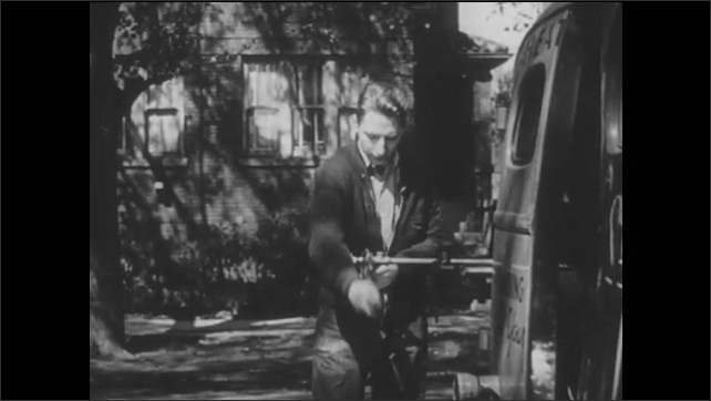 1950s: A plumber steps away and his apprentice picks up a wrench and works on a pipe.