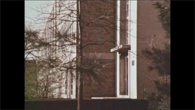 1960s: UNITED STATES: man walks towards building. Man opens door. Room 258. Research Professor enters room. Notre Dame University.