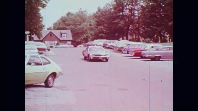 1970s: Police officer drives car. Police car pulls into parking lot.