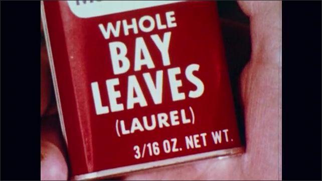 1970s: Mountain laurel leaves and flowers. Container of bay leaves. Peaches cut in half, peach pit.